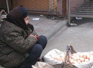 军用胶鞋,坐着一个小板凳在卖鸡蛋.她的前面放着一个大筐子,里边...