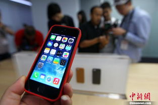 资料图:2013年9月11日,媒体记者在试用iPhone5s及iPhone5c.当...