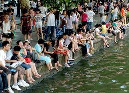 【湖边洗玉足】2011年7月10日,杭州西湖白堤,许多游人坐在西湖边...