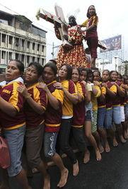 ...游行期间,信徒身穿栗色服装,赤脚,抬着雕像,穿过马尼拉街道....