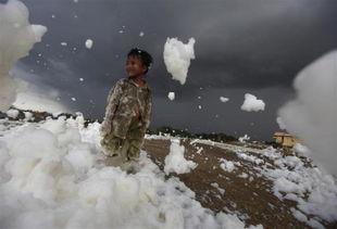 污一点的网名男生-...雅加达,一名小男孩站在泡沫中.泡沫来自一条被污染的河流.-残酷...