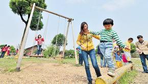 ...长沙市民出游的主要方式.图为在和道源儿童游乐场内,家长带着孩...