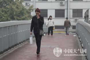 天桥上的行人,捏住鼻子希望减少吸入的污染物.(摄影:关禺)-北...